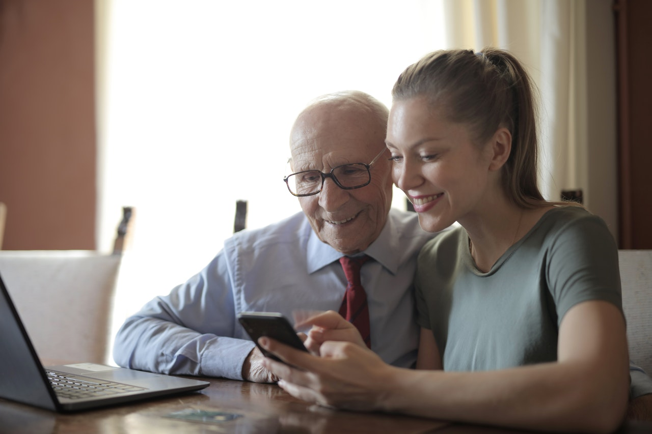 Elderly dad with his adult daughter; smiling together