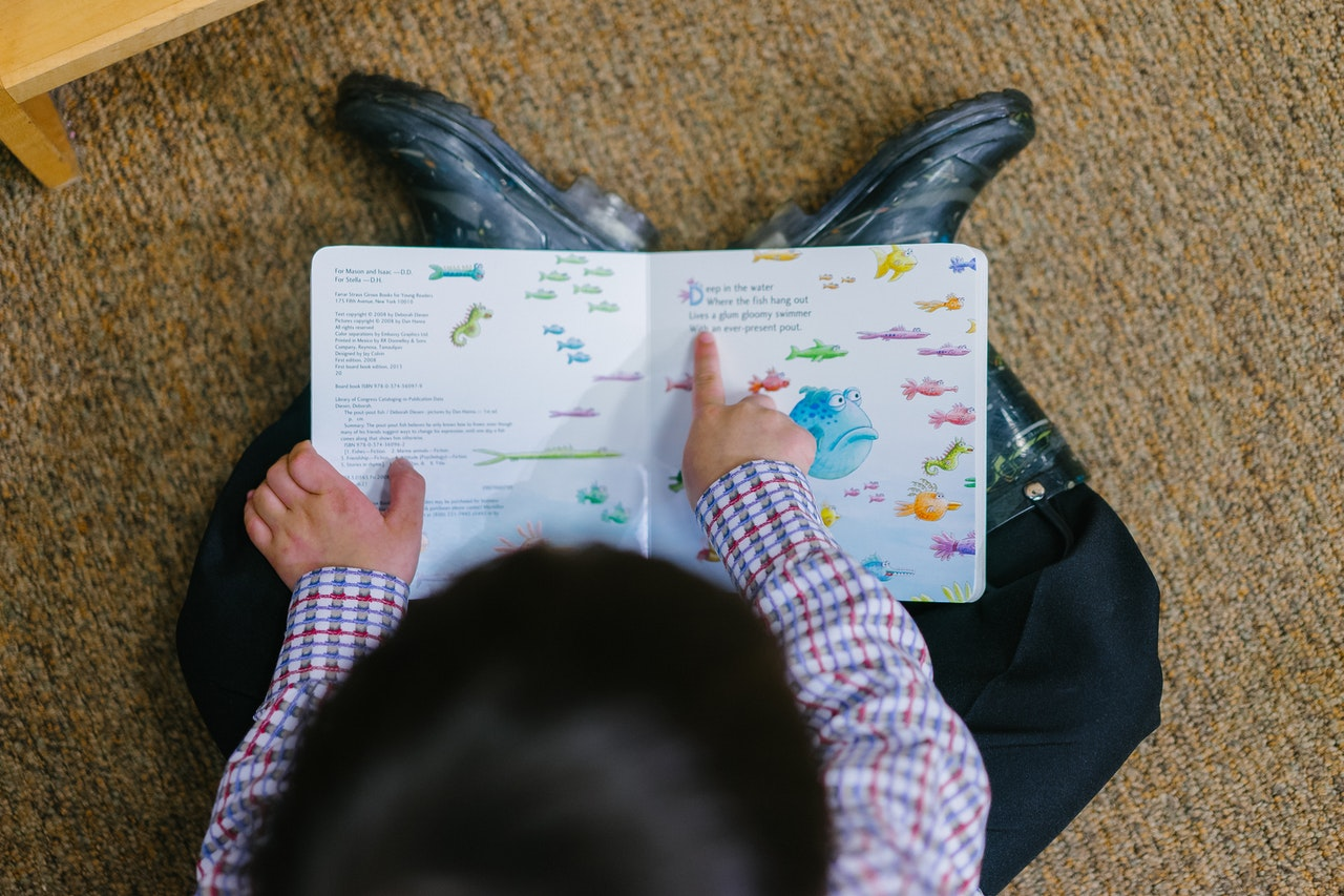 Toddler reading a book to his father, pointing to the words on the page